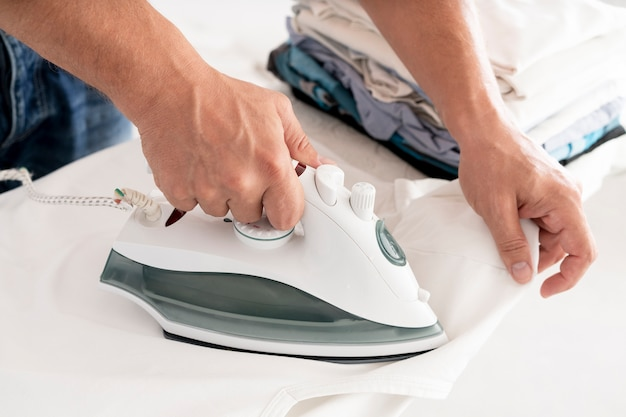Man ironing clothes side view Free Photo