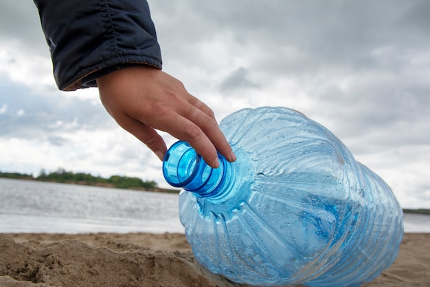A man is cleaning up garbage and plastic bottles on dirty beach by collecting them. environmental pollution Premium Photo