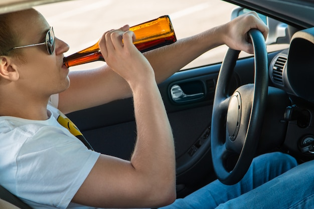 Man is drinking beer in his car Premium Photo
