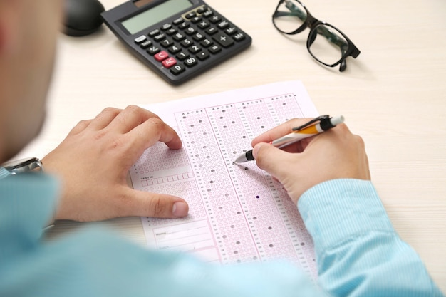 Man is filling omr sheet with pen Premium Photo