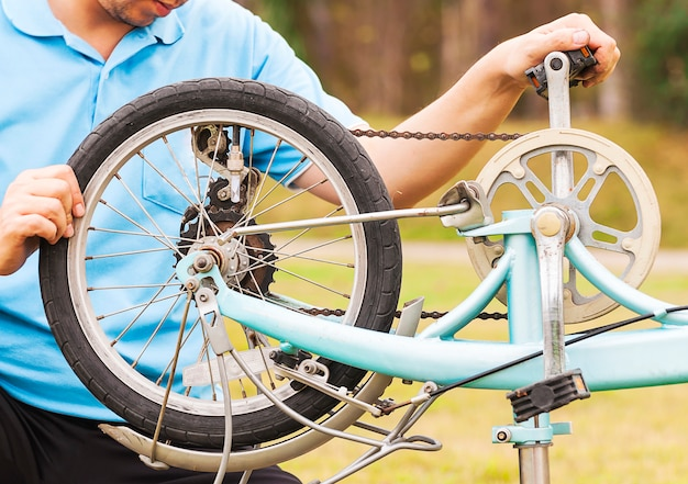 Man is fixing bicycle. photo is focused at a wheel. Free Photo