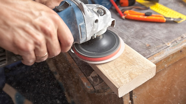 The man is grinding the wooden panel Premium Photo