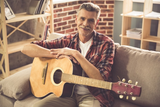 Man is holding a guitar, looking at camera and smiling. Premium Photo
