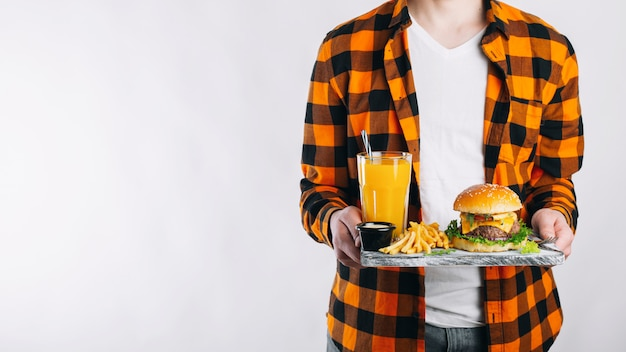A man is holding his lunch on a tray. Premium Photo