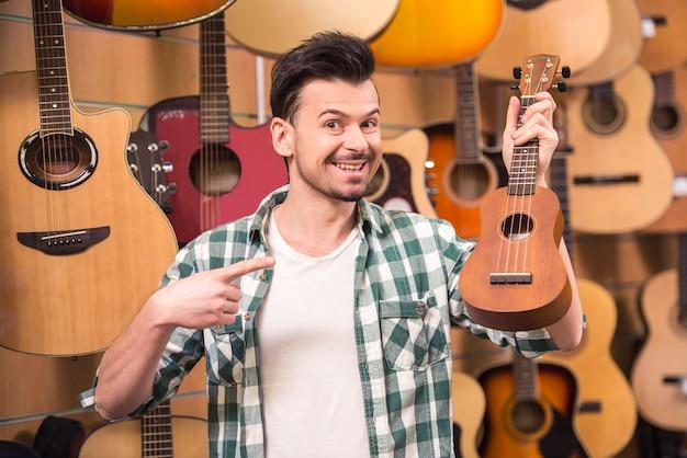 Man is holding ukelele in music shop. Premium Photo