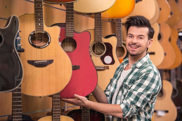 Man is looking and holding guitar in music shop. Premium Photo