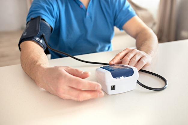 Man is measuring blood pressure with monitor in home. Premium Photo