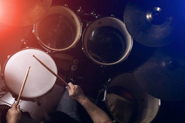 The man is playing drum set in low light background. Premium Photo