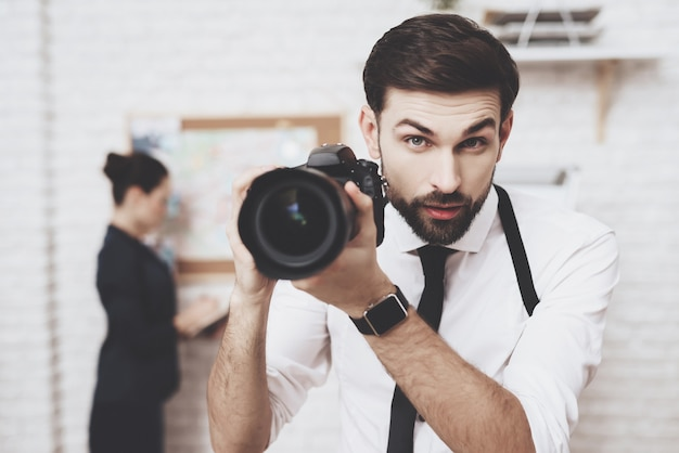 Man is posing with camera, woman is looking at clues map. Premium Photo