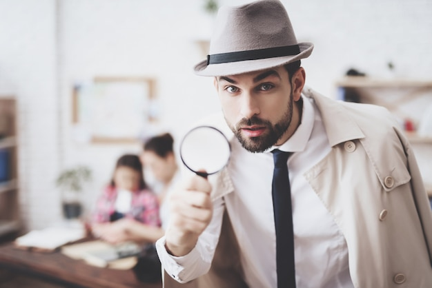Man is posing with magnifying glass. Premium Photo