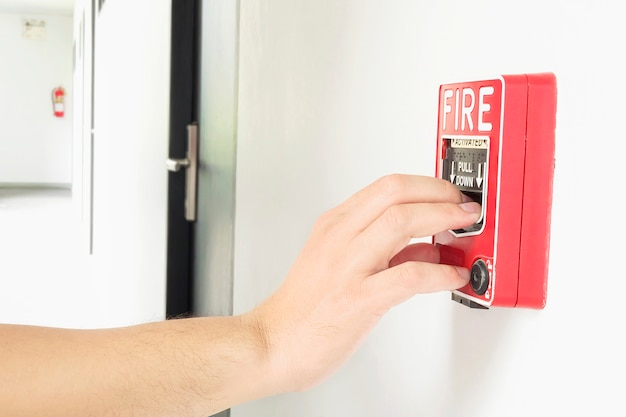 Man is reaching his hand to push fire alarm hand station Free Photo
