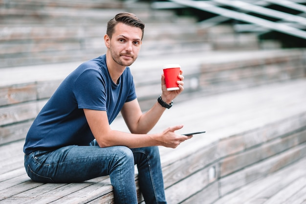 Man is reading text message on mobile phone while walking in the park Premium Photo