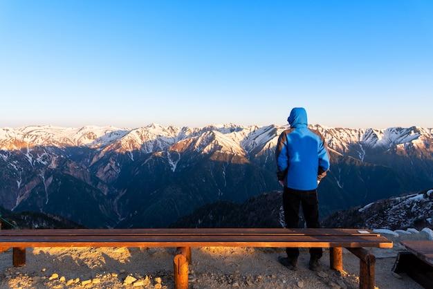 A man is seeing the scenery of mount tsubakuro dake at sunset. snow mountain range of norther japan alps chubu-sangaku park. Premium Photo