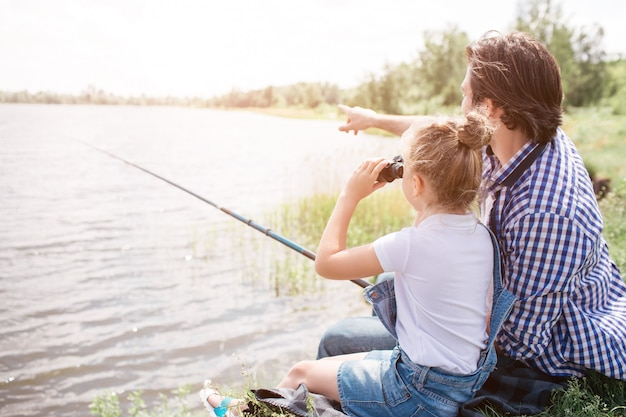 Man is sitting on grass near water with his daughter and pointing forward. girl is looking there through binoculars. he is holding fish-rod in hands. Premium Photo