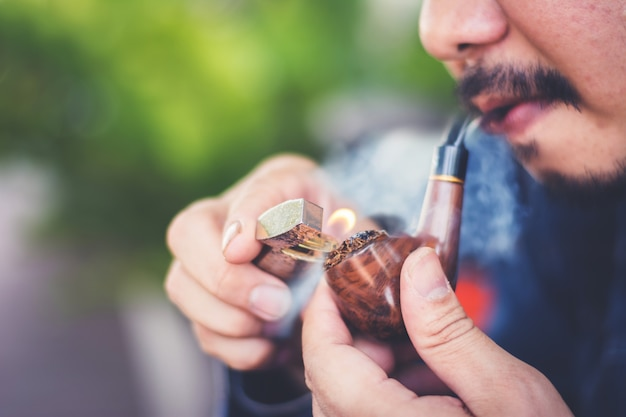 Man is sitting and smoking pipe at public outdoor Premium Photo