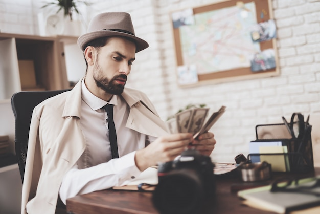 Man is sitting at table counting money. Premium Photo