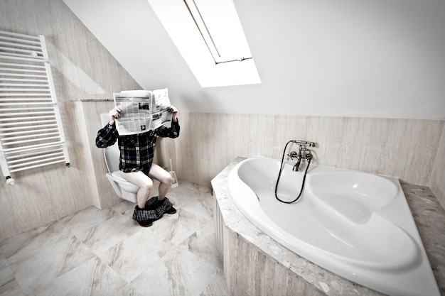 Man is sitting on the toilet. Free Photo