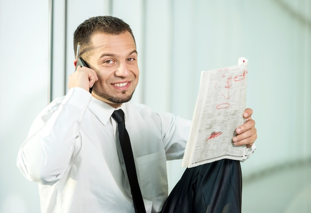 A man is sitting with a newspaper and speaking by phone. Premium Photo