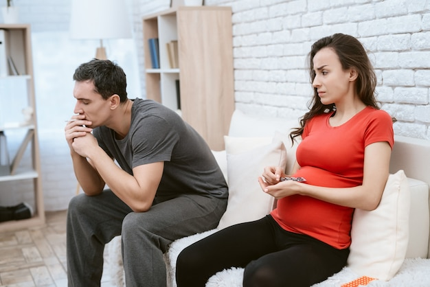 Man is smoking a cigarette next to him is his pregnant wife. Premium Photo