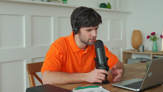 Man is speaking in microphone in studio recording podcast gesturing expressing opinions for online blog. Premium Photo