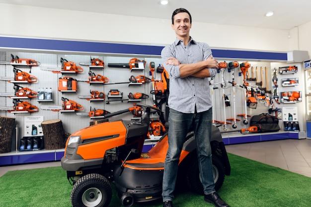 A man is standing near a lawn mower. Premium Photo
