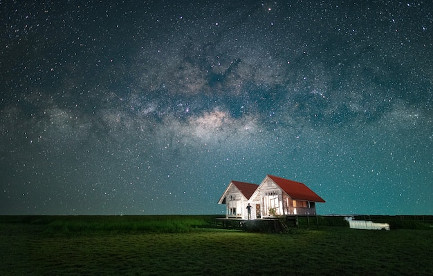 A man is standing of the twin house next to the milky way galaxy Premium Photo