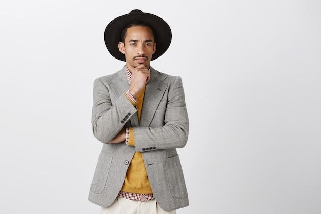 L'uomo non è sicuro di te. ritratto di dubbio maschio di bell'aspetto in giacca e cappello alla moda, tenendo la mano sul mento, accigliato, sospettoso mentre pensa, dubbioso o incredulo sul muro grigio Foto Gratuite