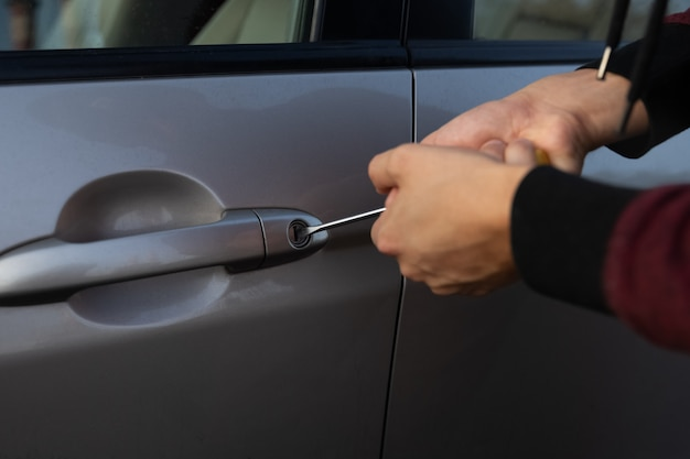 A man is trying to break the car lock in order to steal it from the parking lot. Premium Photo