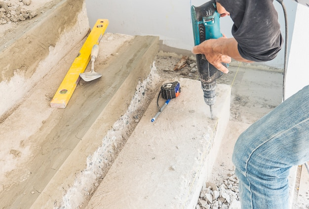 Man is working with reinforce concrete stair structure modification using hand drill Free Photo