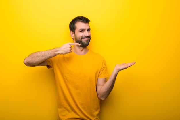 Man on isolated vibrant yellow color holding copyspace imaginary on the palm to insert an ad Premium Photo