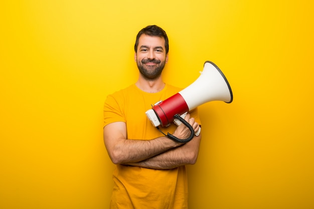 Man on isolated vibrant yellow color holding a megaphone Premium Photo