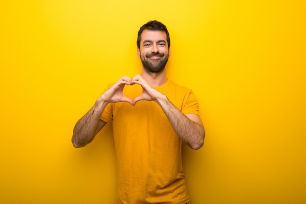 Man on isolated vibrant yellow color making heart symbol by hands Premium Photo