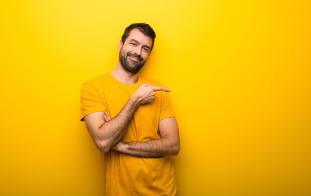 Man on isolated vibrant yellow color pointing finger to the side in lateral position Premium Photo