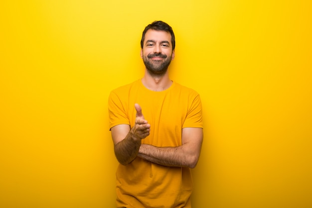 Man on isolated vibrant yellow color shaking hands for closing a good deal Premium Photo