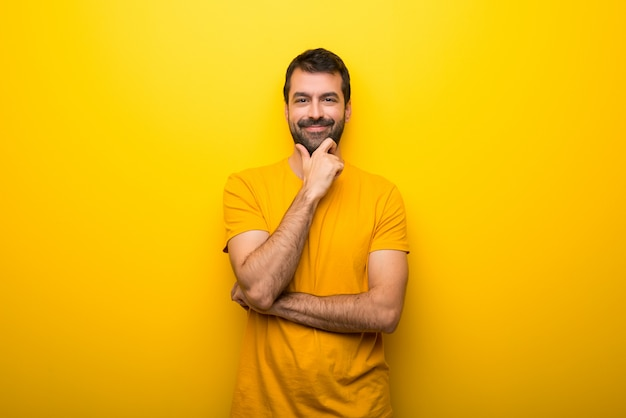 Man on isolated vibrant yellow color smiling and looking to the front with confident face Premium Photo