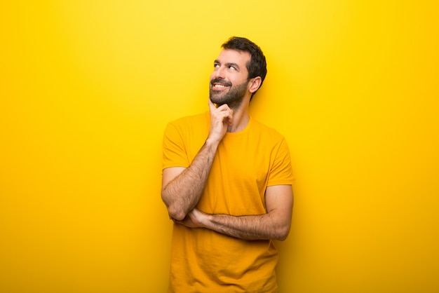 Man on isolated vibrant yellow color thinking an idea while looking up Premium Photo