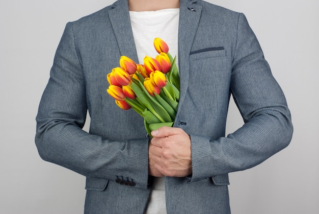 Man in a jacket holding a bouquet of tulips | Premium Photo