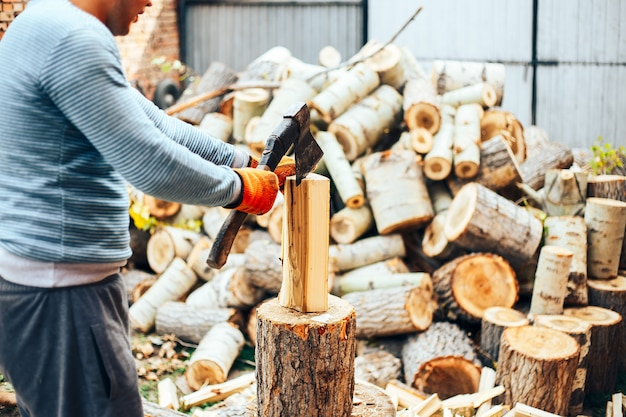 Man in jeans and checkered shirt standing near stump with ax in hands Premium Photo