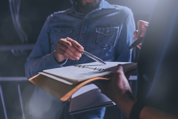 Man in jeans gives advice on work in a notebook with colleagues in office. Premium Photo
