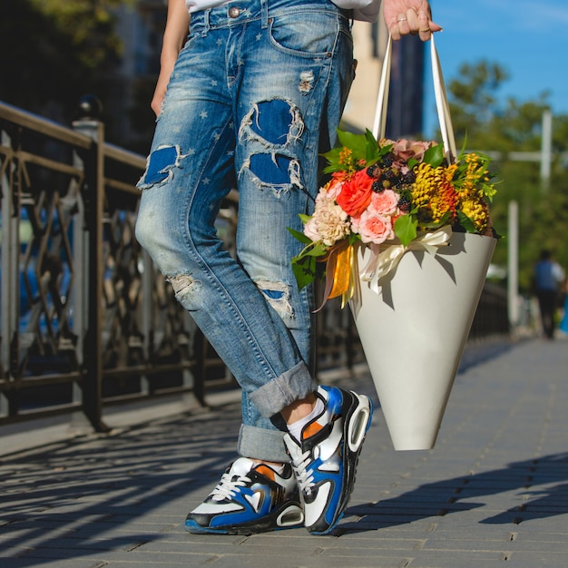 Man in jeans with a cardboard bouquet of flowers. Free Photo