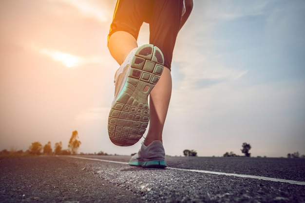 Man jogging on a road with the sun. Premium Photo