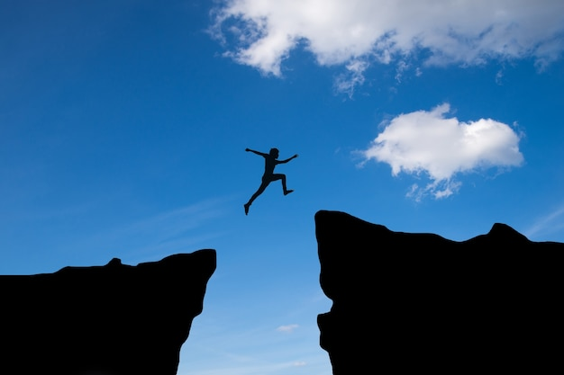 Man jump through the gap between hill.man jumping over cliff on blue sky ,business concept idea Free Photo