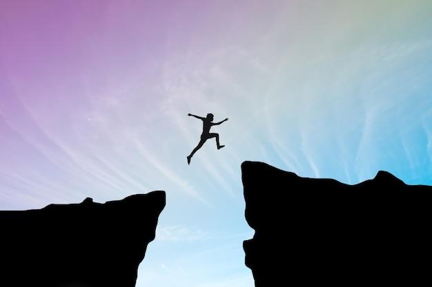 Человек прыгать через разрыв между hill.man прыгает через скалу на голубом небе, концепция концепции бизнеса Бесплатные Фотографии
