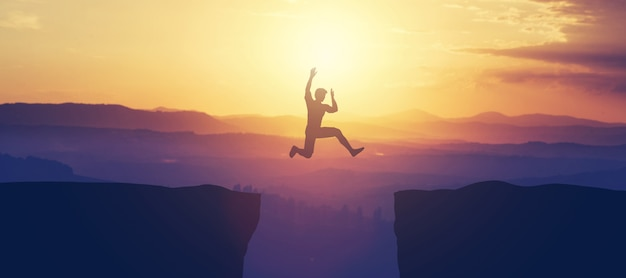 Man jumping above the cliff in the mountains. Premium Photo