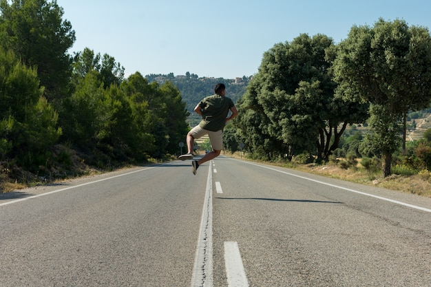 Man jumping on the empty road. globetrotter Premium Photo