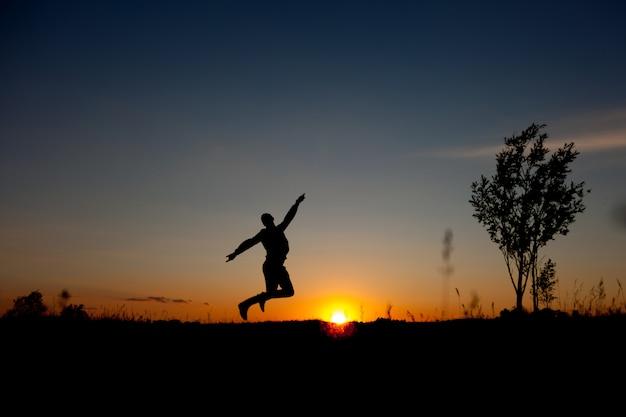 Premium Photo | Man jumping sunset background. happy man