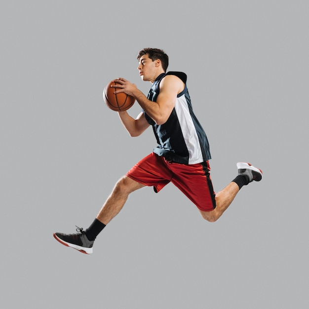 Man jumping while holding a basketball Free Photo
