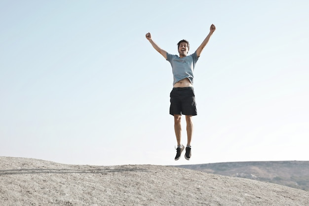 Man jumping with arms up depicting freedom or success Free Photo