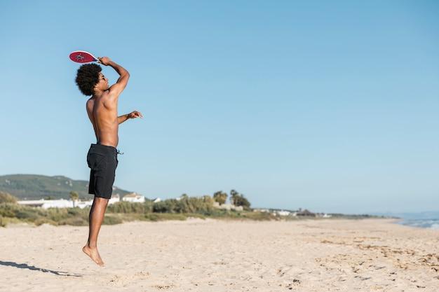 男はビーチでテニスラケットでジャンプ 無料写真