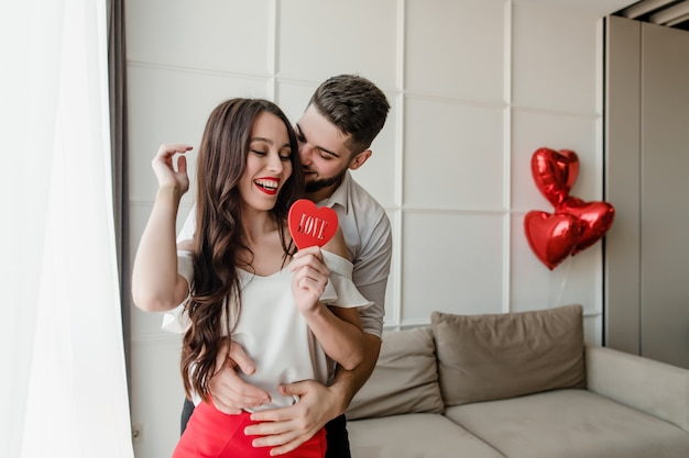 Man kisses woman at home with heart shaped figure with word love and balloons on couch Premium Photo